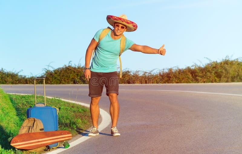 Hübscher junger Mann, der entlang einer ländlichen Gebirgsstraße per Anhalter fährt - Wandererkerl mit Gepäck und longboard versu lizenzfreie stockfotos