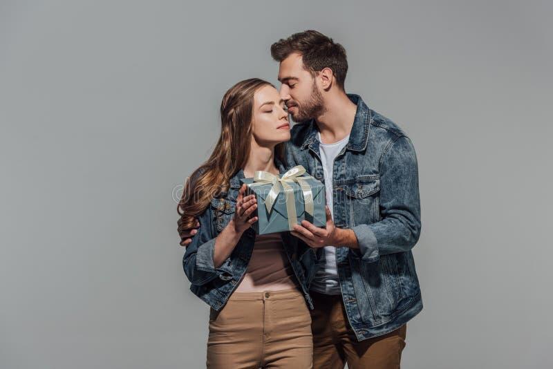 Hübscher junger Mann, der Freundin küsst und Geschenkbox darstellt stockfotos