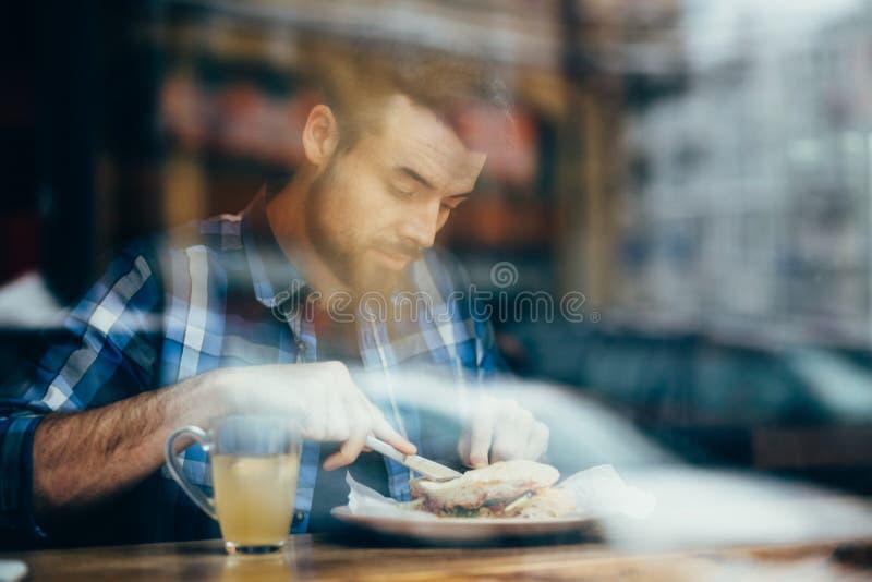 Hübscher junger Mann, der im eleganten Restaurant allein zu Mittag isst stockfoto