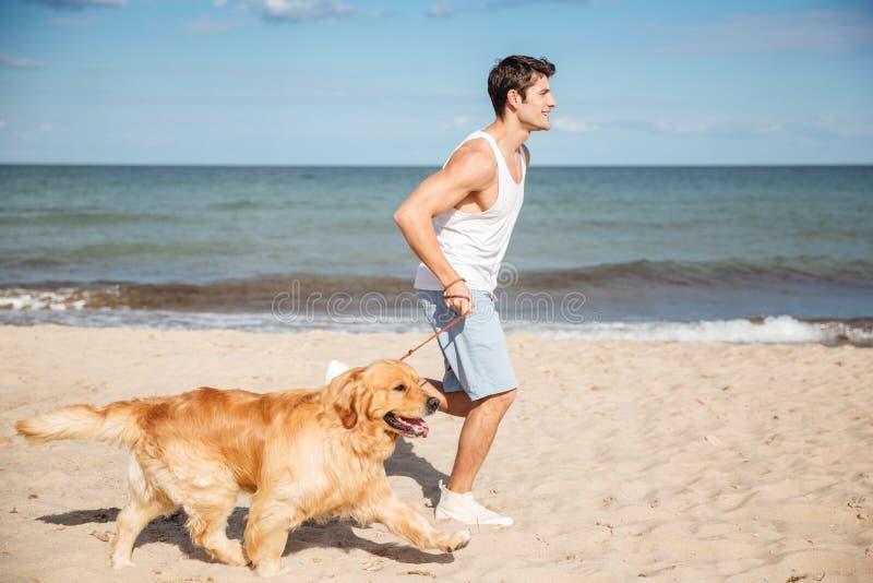 Hübscher junger Mann, der mit Hund auf dem Strand läuft stockbild