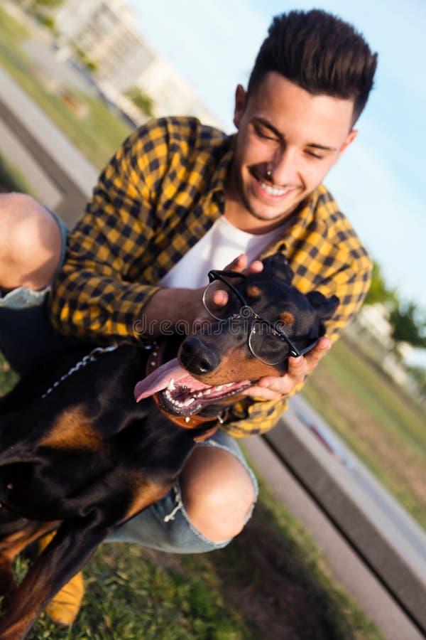 Hübscher junger Mann, der mit seinem Hund im Park spielt lizenzfreie stockfotografie