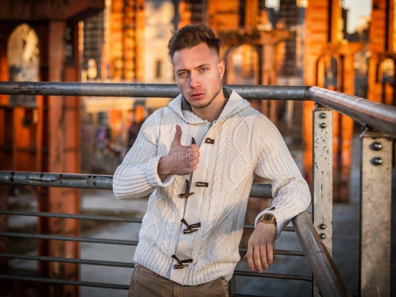Hübscher junger Mann, der OKAYzeichen mit dem Daumen oben im Freien tut lizenzfreie stockbilder