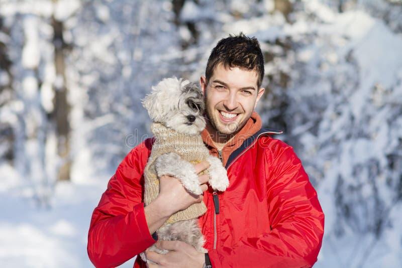 Hübscher junger Mann, der seinen kleinen weißen Hund im Winter umarmt snowing lizenzfreies stockfoto