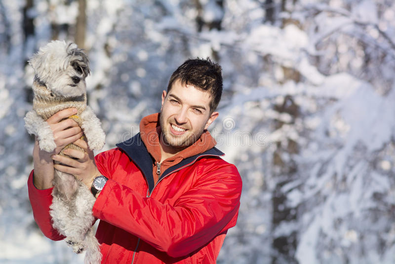 Hübscher junger Mann, der seinen kleinen weißen Hund im Winter umarmt snowing lizenzfreie stockbilder