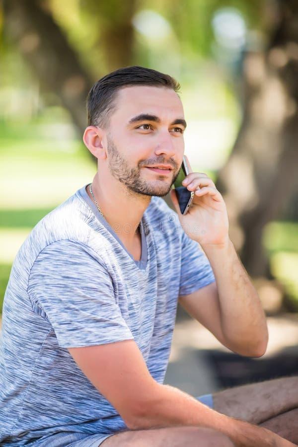 Hübscher junger Mann, der am Telefon beim Sitzen auf Bank im Park spricht lizenzfreies stockfoto