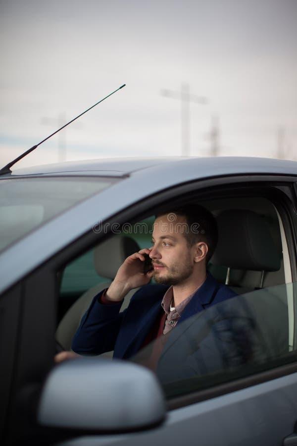 Hübscher junger Mann, der um sein Mobiltelefon ersucht stockfoto