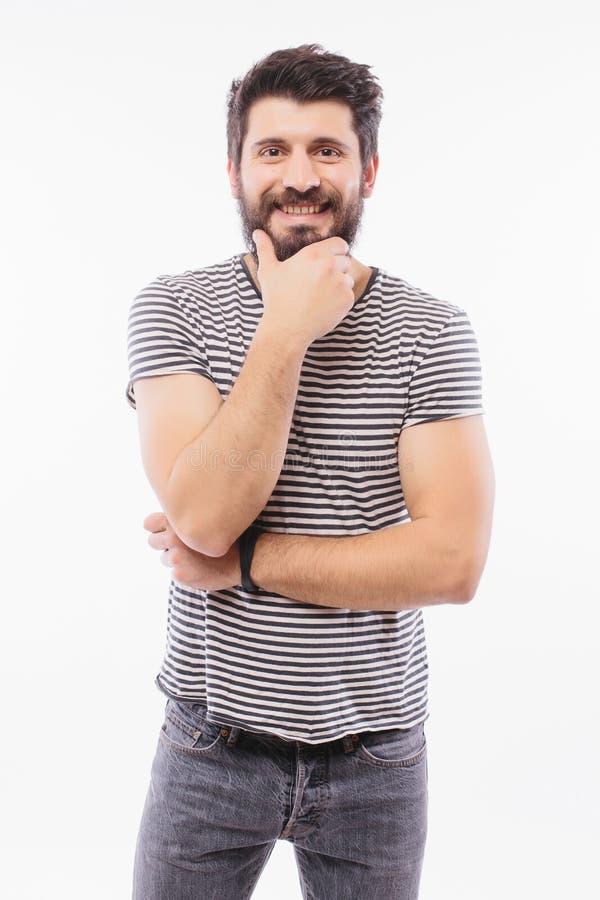 Hübscher junger Mann des Porträts mit der Hand auf dem Bartlächeln stockfotografie