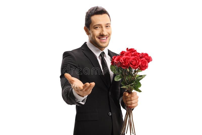 Hübscher junger Mann in einer Klage, die ein Bündel rote Rosen hält und an der Kamera mit seiner Hand darstellt stockbilder