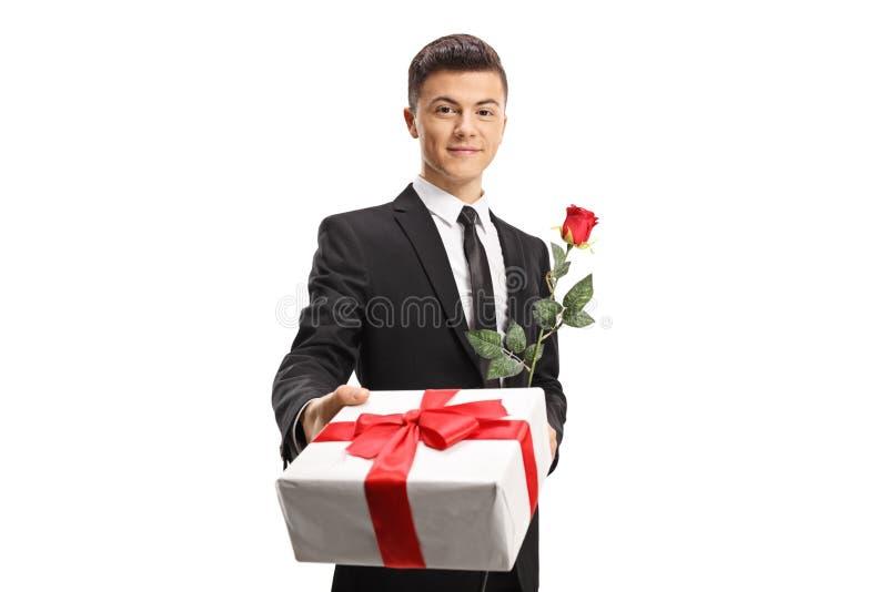 Hübscher junger Mann in einer Klage, die ein Geschenk und eine rote Rose gibt stockfoto