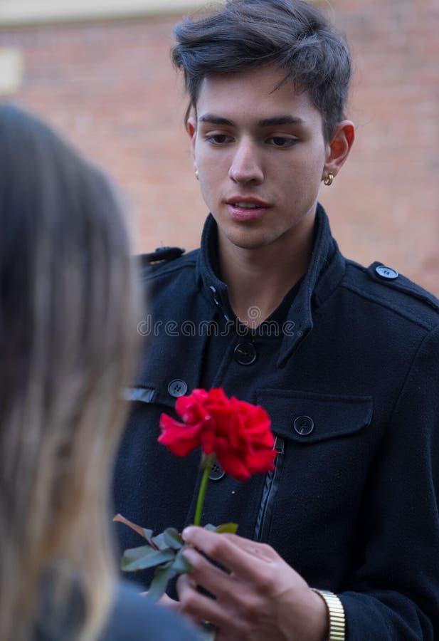 Hübscher junger Mann gibt der Frau Blume lizenzfreie stockbilder
