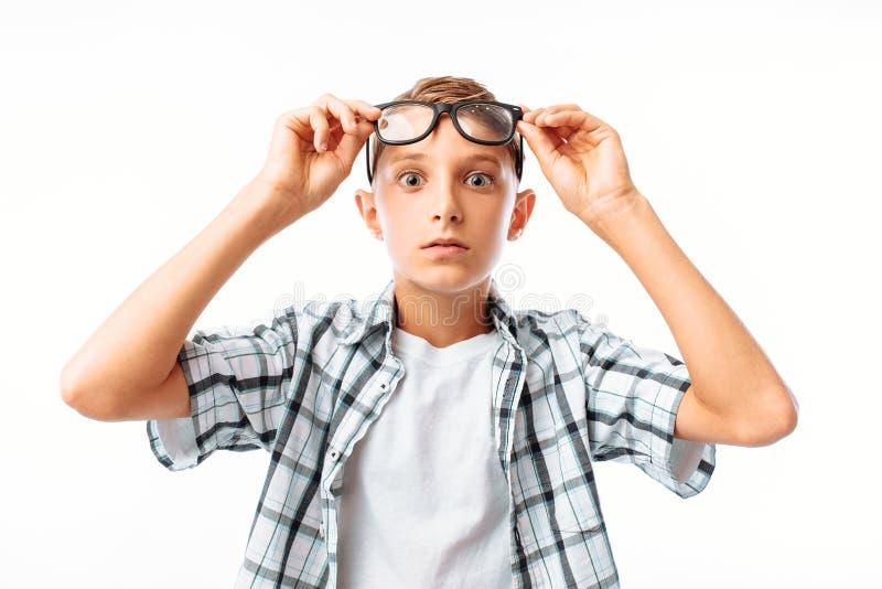 Hübscher junger Mann hebt Gläser auf Stirn in der Überraschung an, der jugendlich entsetzte Junge, im Studio auf weißem Hintergru stockfoto
