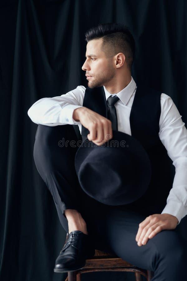 H?bscher junger Mann im eleganten Anzug mit Hut in den H?nden, die auf schwarzem Hintergrund aufwerfen lizenzfreies stockfoto
