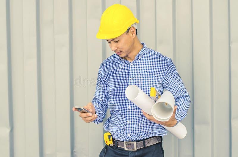 Hübscher junger Mann im Hardhat, der Plan hält und Handy verwendet, bei draußen stehen und gegen Gebäudestruktur stockbild