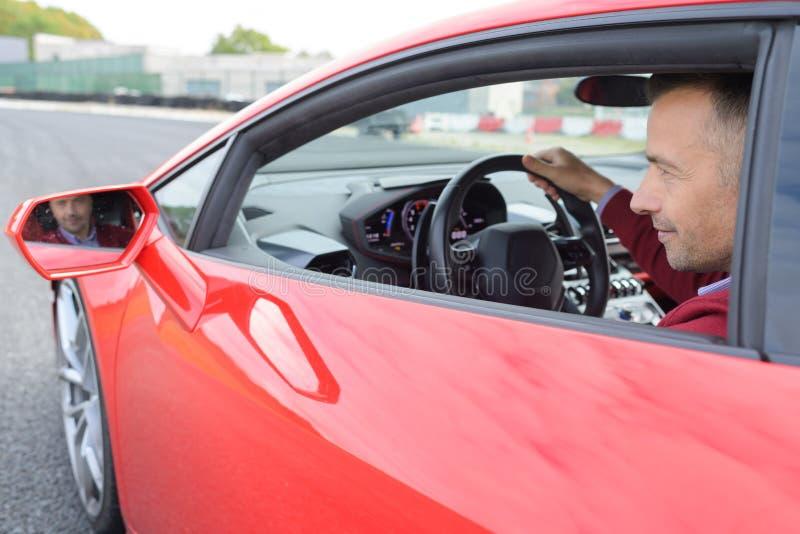 Hübscher junger Mann im neuen Sportauto stockbilder