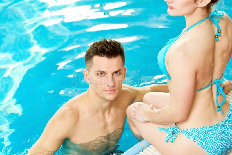 Hübscher junger Mann im Pool stockfotos
