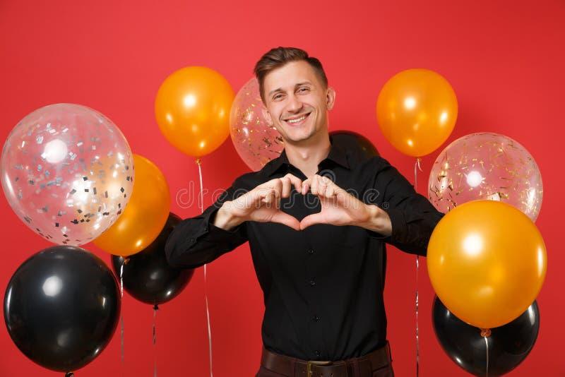 Hübscher junger Mann im schwarzen klassischen Hemd, das Herzgeste auf hellen roten Hintergrundluftballonen zeigt St.-Valentinsgru stockbild