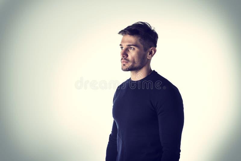 Hübscher junger Mann mit blauem Pullover lizenzfreies stockbild