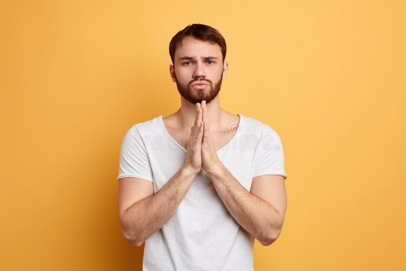 Hübscher junger Mann mit dem Plädieren des bittenen Ausdrucks, hält Palmen zusammen stockfoto
