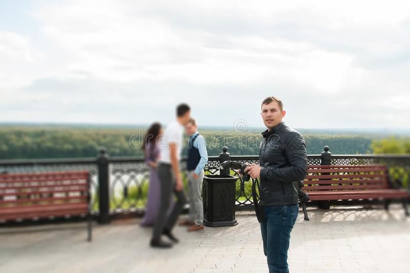 Hübscher junger Mann mit Digitalkamera bei draußen stehen stockfotografie