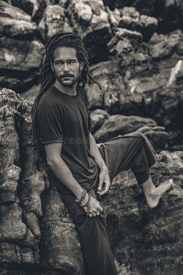 Hübscher junger Mann mit Dreadlocks draußen männliches Modell an den Felsen stockfotografie
