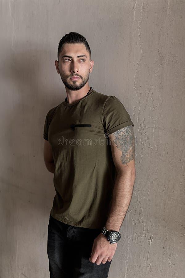 Hübscher junger Mann mit einer stilvollen Frisur gekleidet in den Ständen der zufälligen Kleidung auf dem Wandhintergrund stockbild