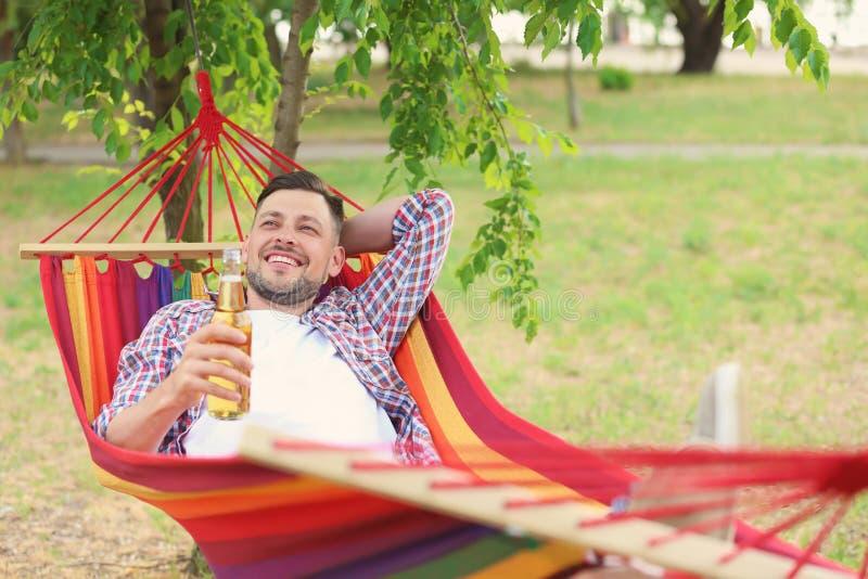 Hübscher junger Mann mit Flasche des Bierstillstehens stockfoto