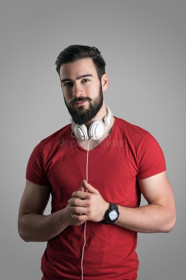Hübscher junger Mann mit Kopfhörern im roten T-Shirt, das Kamera betrachtet stockfotografie