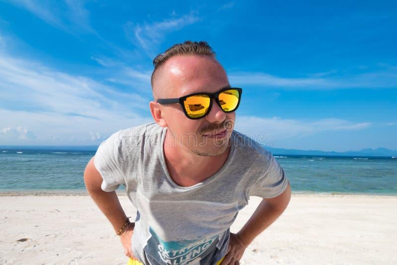 Hübscher junger Mann mit Sonnenbrille gegen hellen Strandhintergrund und den blauen Indischen Ozean Es gibt einen Vulkan Agung stockbild