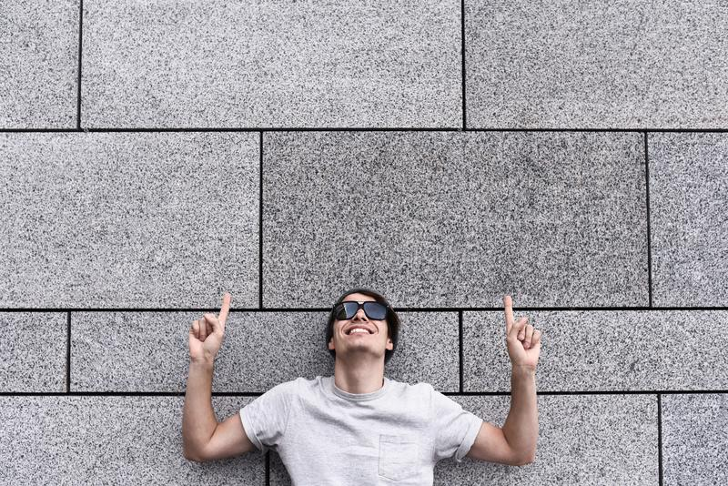 Hübscher junger Mann mit Sonnenbrille zeigt weg, oben schauen und das Lächeln und steht gegen graue Wand lizenzfreie stockfotografie