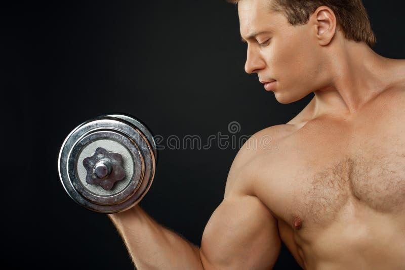 Hübscher junger Mann trainiert mit Eisen stockfotografie