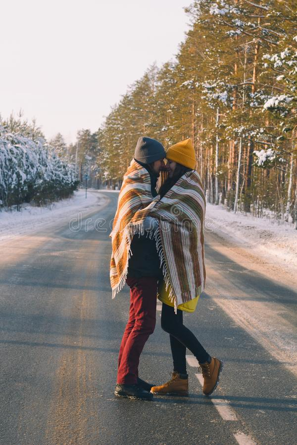 Hübscher junger Mann und schöne junge Frau unter woolen Plaid im Winterwald stockfoto