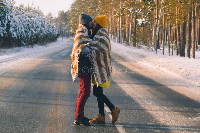 Hübscher junger Mann und schöne junge Frau unter woolen Plaid im Winterwald stockbild