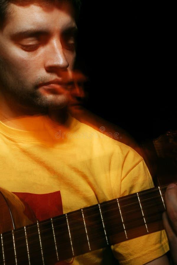 Hübscher junger Musiker, der auf Gitarre spielt Doppelbelichtungskonzept lizenzfreie stockfotografie