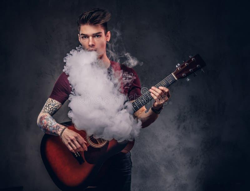 Hübscher junger Musiker mit dem stilvollen Haar in einem T-Shirt, atmet Rauch beim Spielen der Akustikgitarre aus stockfotografie