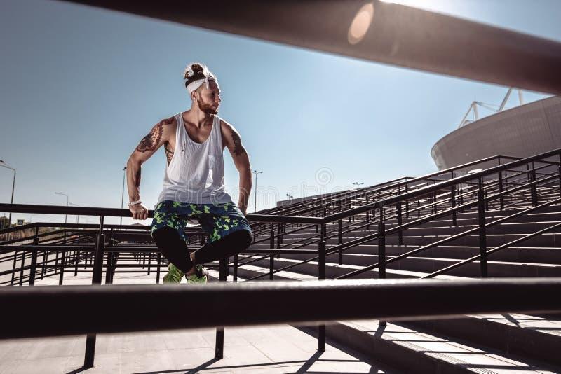 Hübscher junger muskulöser Mann in der modernen Sportkleidung, die nach der Ausbildung auf den Schritten nahe bei Stadion an hell stockfotos