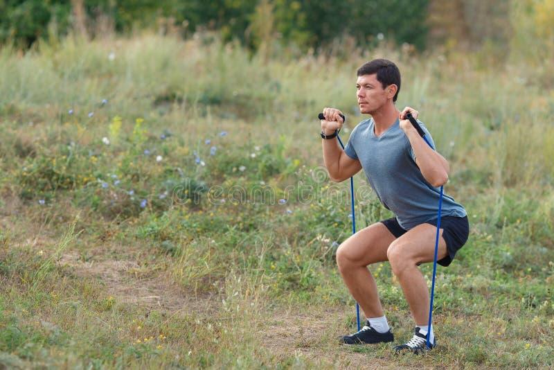 Hübscher junger muskulöser Sport bemannt die Ausübung der Außenseite, die mit Gummiband im Freien ist stockfotografie