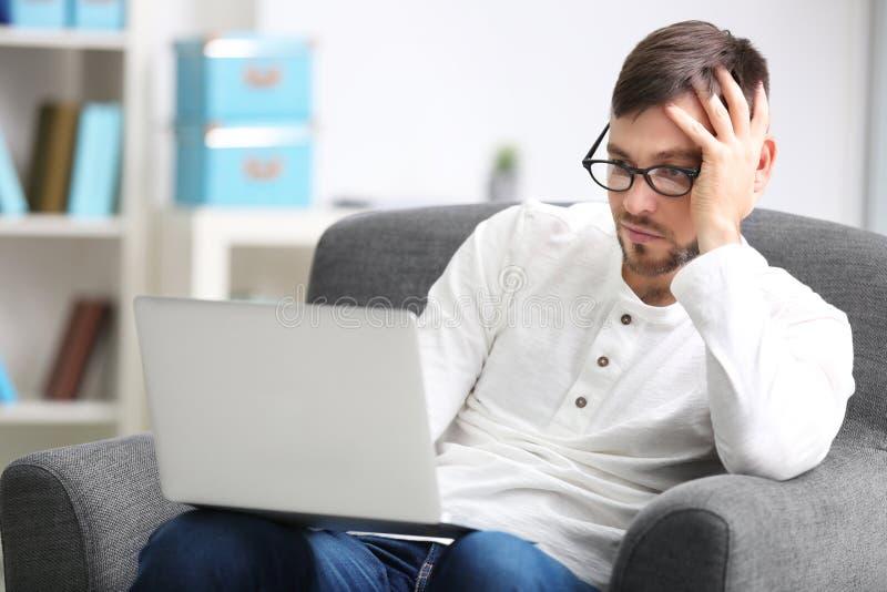 Hübscher junger Programmierer, der mit Laptop arbeitet stockbild