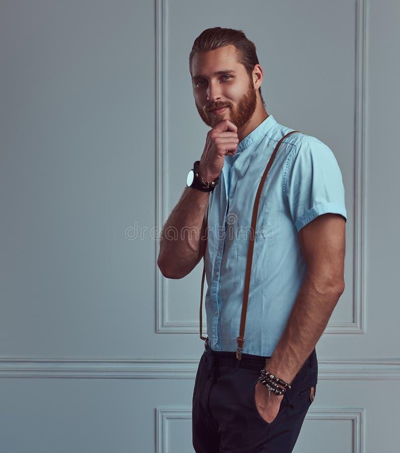 Hübscher junger Retro- stilvoller Rothaarigemann in den Hosenträgern, die gegen eine weiße Wand in einem Studio aufwerfen stockfotos