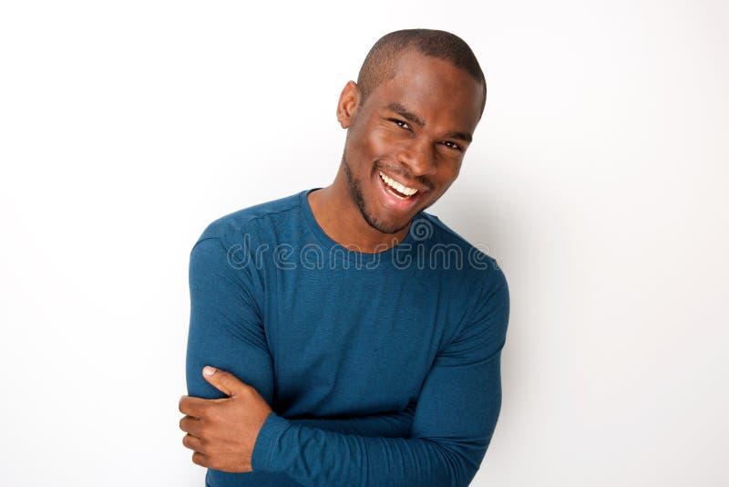 Hübscher junger schwarzer Mann, der mit den Armen gefaltet durch weißen Hintergrund lächelt lizenzfreies stockfoto