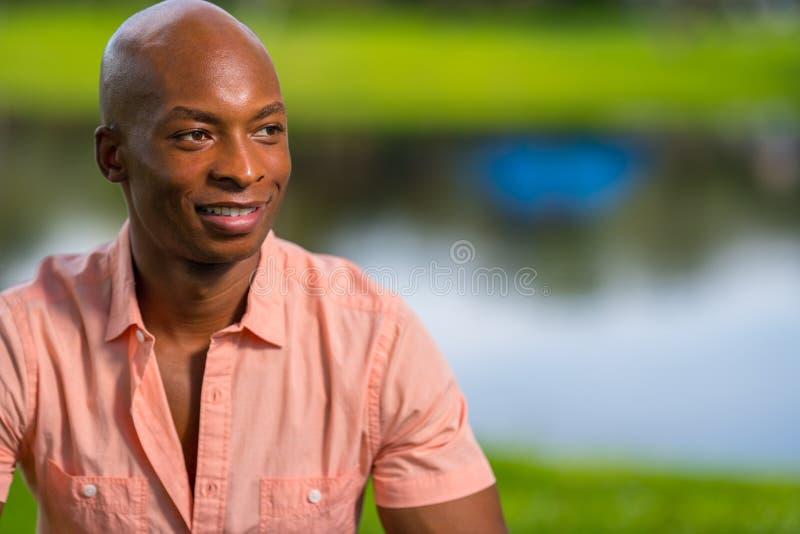 Hübscher junger schwarzer Mann des Porträts, der in einer Parkeinstellung aufwirft angenehme bokeh Seelandschaft im Hintergrund stockfotografie
