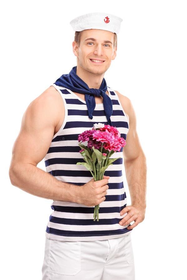 Hübscher junger Seemann, der einen Blumenstrauß von Blumen hält stockfoto
