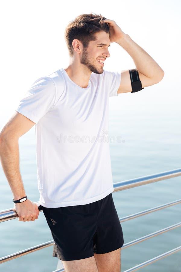 Hübscher junger Sportler, der am Pier nach Training stillsteht lizenzfreie stockfotos