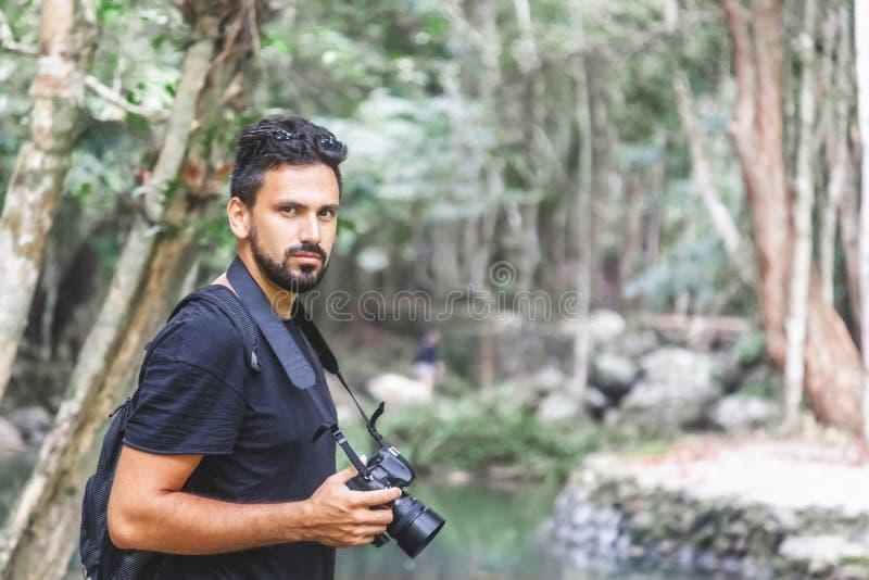 Hübscher junger stilvoller männlicher Fotograf im schwarzen T-Shirt und in der Sonnenbrille nimmt an Trekking im grünen Dschungel stockfotos
