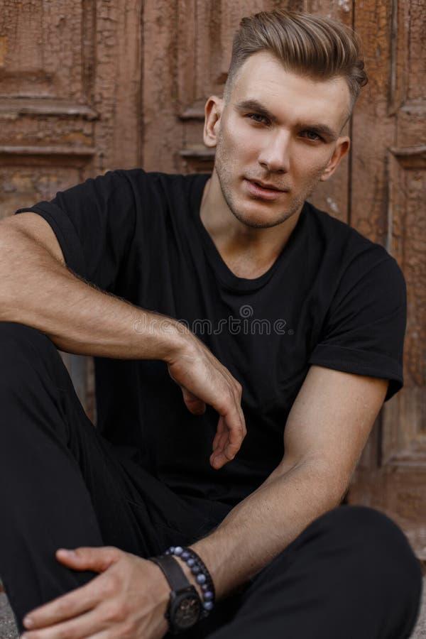 Hübscher junger stilvoller Mann mit Frisur in der schwarzen Kleidung stockbilder