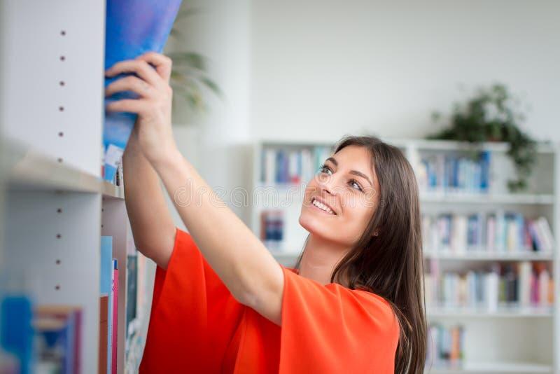 Hübscher, junger Student, der nach einem Buch im ibrary sucht stockbilder
