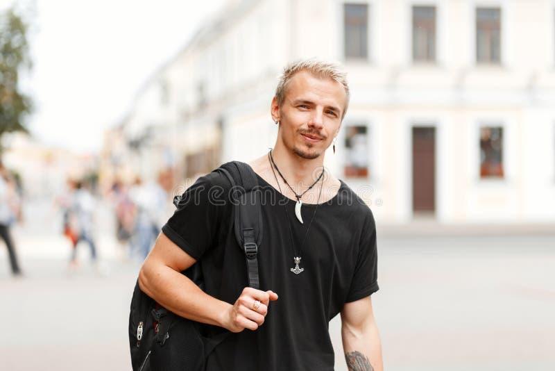 Hübscher junger touristischer Mann in einem schwarzen stilvollen T-Shirt lizenzfreies stockfoto