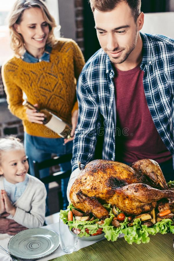 hübscher junger Vater, der Danksagungstruthahn auf Feiertagstabelle während aufgeregtes Frau- und Tochterschauen setzt lizenzfreie stockfotografie