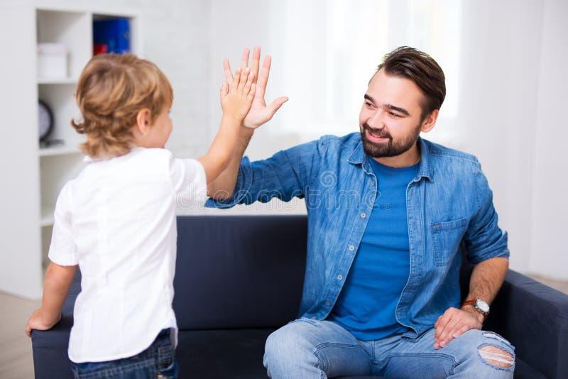 Hübscher junger Vater, der seinem kleinen Sohn hohen fünf gibt stockfotografie