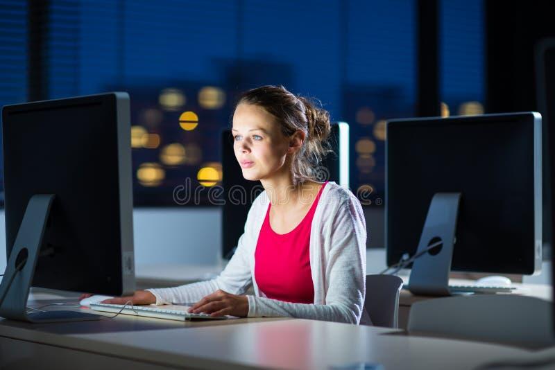 Hübscher, junger weiblicher Student, der einen Desktop computer/pc verwendet stockbilder