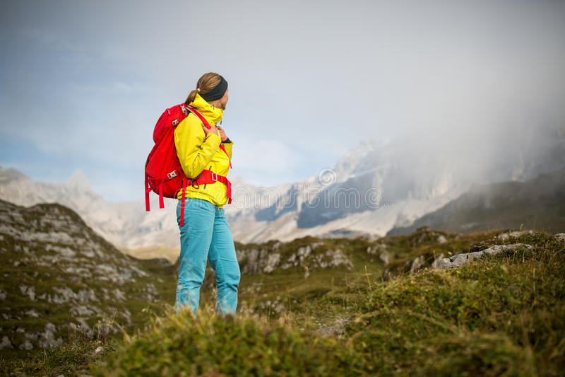 Hübscher, junger weiblicher Wanderer, der in Hochgebirge geht stockfoto
